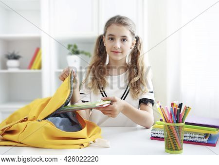 Pupil Child Put Books And Notes Into Backpack. School Supplies.back To School Concept. School Girl P