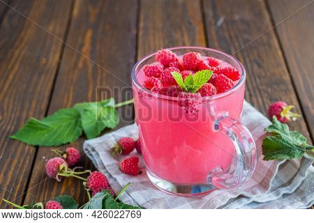 Traditional Russian Hot Drink Raspberry Jelly Or Kissel In A Glass Transparent Mug On A Brown Wooden