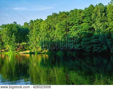The Beautiful And Peaceful View On The River And The Green Trees On Its Bank. The Spring Or Summer B