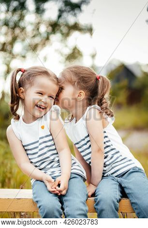 Twin Sisters Play Outdoors In Summer Day