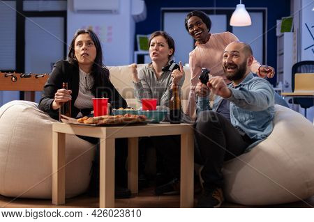 Colleagues With Diverse Ethnicity Enjoy Togetherness At Office After Work Playing Console Game On Tv