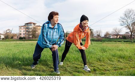 Smiling Grandmother And Granddaughter Doing Sports Warm-up Together It The Park. Old And Young Women