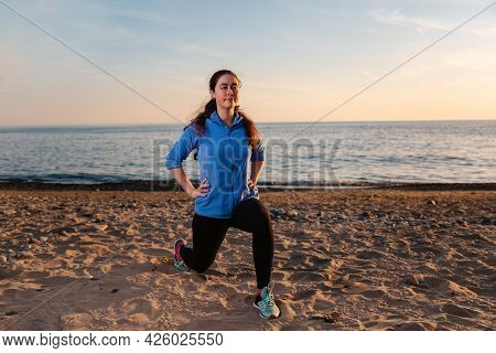 A Young Smiling Woman Plays Sports On The Sandy Beach Of The Ocean. Outdoor. Sports And Healthy Life