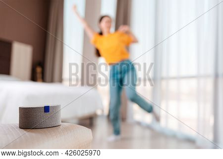 A Portable Smart Gray Speaker Plays Music. In The Background, A Woman Dances In A Blur. The Concept