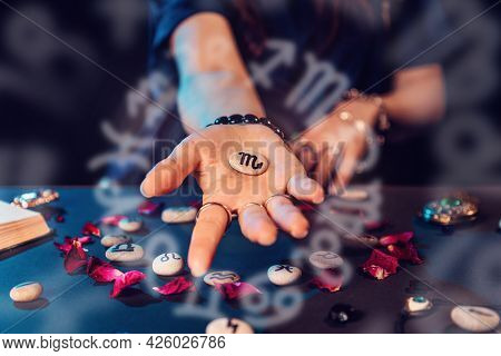 Astrology And Horoscope. A Woman's Hand Holds A Stone With The Sign Of The Zodiac. Close Up. The Con