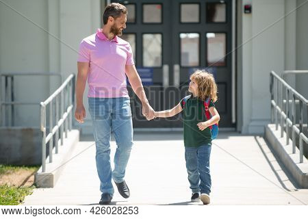 Father Supports And Motivates Son. Parent Taking Child To School. Pupil Of Primary School Go Study W