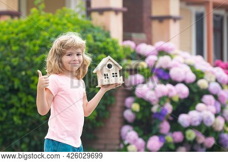 Kid Dreaming Of New Home. Happy Boy Holding Dream House, Show Thumbs Up. Home Insurance Concept. Mor