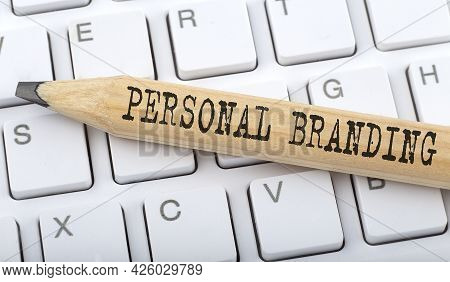Text Personal Branding On Wooden Pencil On White Keyboard. Business