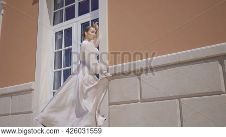 Stylish Model In Sexy Outfit At Building. Action. Model In Extravagant Outfit Poses On Background Of