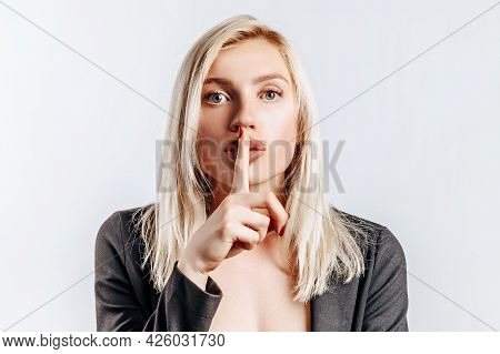 Beautiful Young Serious Girl Showing Hush Gesture, Keep Secret On Gray Isolated Background