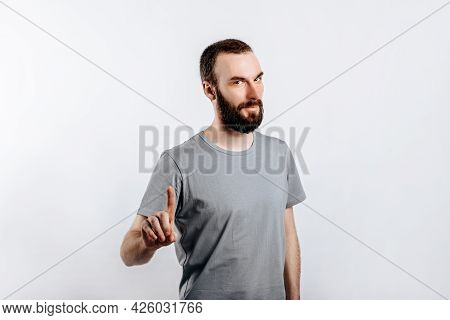 Serious Puzzled Handsome Man Pays Attention To A Place For Advertising. A Business Man Offers A Solu