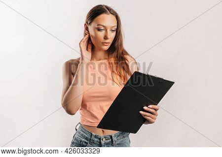 Girl Student Frowns With Displeasure And Reads Information In Documents. Beautiful Young Business Wo