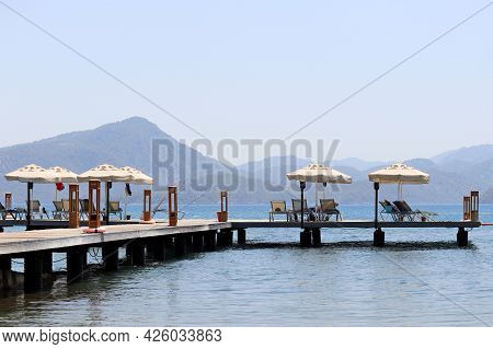 Wooden Pier With Lounge Chairs And Parasols On Sea Resort, Vacation Concept. People Sunbathing On A
