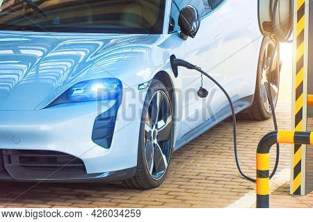 Refueling For Cars E-mobility, With Headlights On And Blue Light. Charging An Electric Car At Hybrid