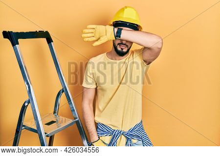Handsome man with beard by construction stairs wearing hardhat covering eyes with arm, looking serious and sad. sightless, hiding and rejection concept