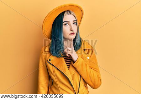 Young modern girl wearing yellow hat and leather jacket thinking concentrated about doubt with finger on chin and looking up wondering