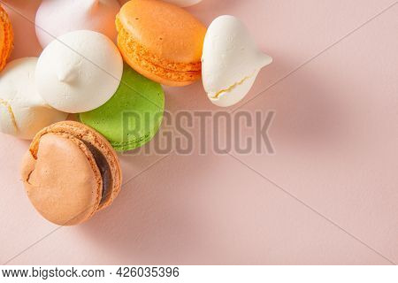 Macaroons, Beige, Peach, Green French Macaroons, White Bizet, Meringue  On Beige Background Top View