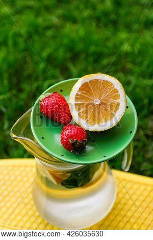 Defocus Saucer With Lemon And Two Strawberry Standing On Glass Jug Of Lemonade With Slice Lemon And