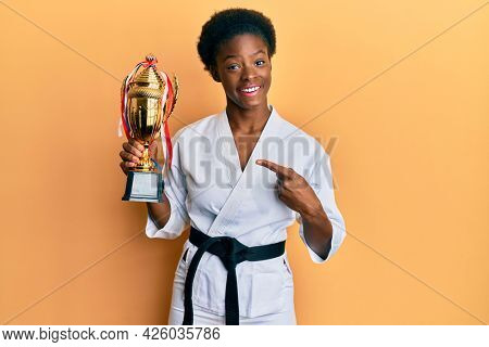 Young african american girl wearing karate kimono holding trophy smiling happy pointing with hand and finger