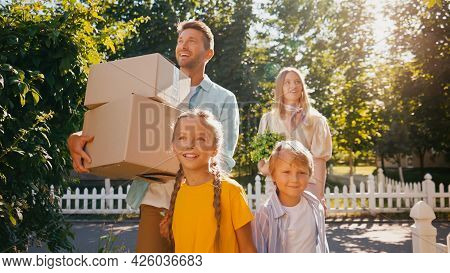 Cheerful Parents Holding Boxes And Plant While Walking With Happy Kids, Relocation Concept.