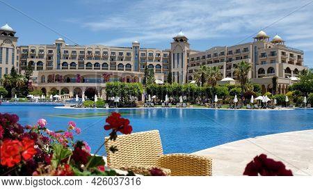 Summer Terrace And Wicker Rattan Chair Near Pool Resort Arabic Style Buildings. Defocused Red Gerani