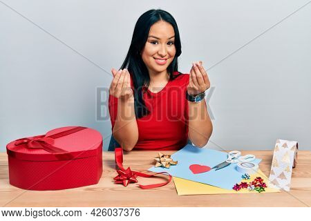 Beautiful hispanic woman with nose piercing doing handcraft creative decoration doing money gesture with hands, asking for salary payment, millionaire business