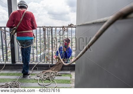 The Builder Is Hanging On The Ropes Working On High Building.
