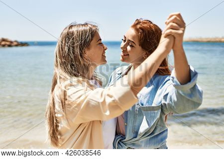 Young lesbian couple of two women in love at the beach. Beautiful women together dancing at the beach