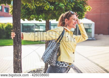 Happy Young Woman Stretching At Tree In Park At Oudoors
