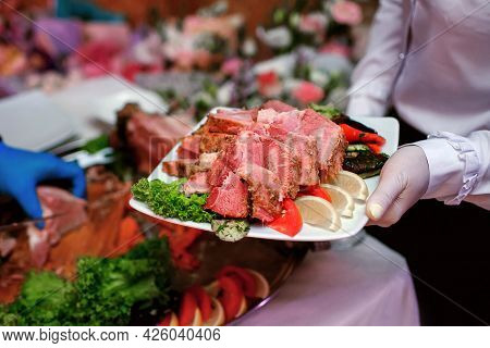 The Waiter Serves Food To The Guests On A White Platter. The Plate Is Filled With Meat Salad And Veg