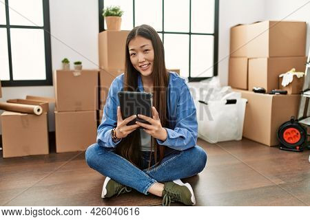 Young chinese girl smiling happy using touchpad sitting on the floor at new home