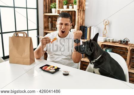 Young hispanic man eating sushi using chopsticks annoyed and frustrated shouting with anger, yelling crazy with anger and hand raised
