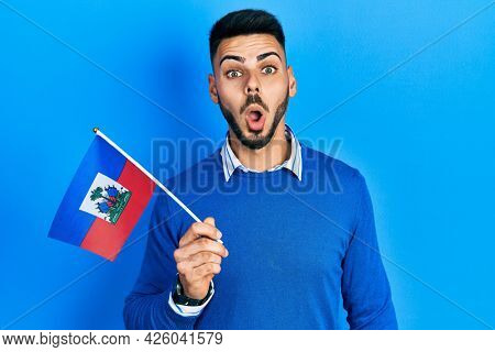 Young hispanic man with beard holding haiti flag scared and amazed with open mouth for surprise, disbelief face