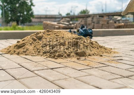 Close-up Of A Pile Of Sand Lying On The New Sidewalk To Seal The Seams Between The Paving Slabs. Lay