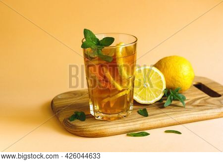 Iced Tea With Lemon Slices And Mint On Wooden Table. Close Up Summer Vitamin Antioxidant Beverage. C