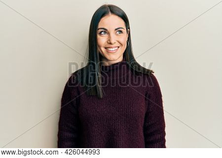 Young brunette woman wearing casual winter sweater looking to side, relax profile pose with natural face and confident smile.