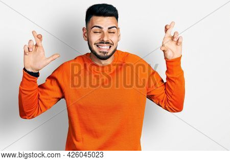 Young hispanic man with beard wearing casual orange sweater gesturing finger crossed smiling with hope and eyes closed. luck and superstitious concept.