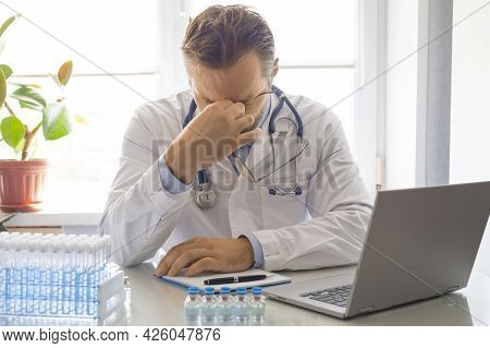 Photo Of A Tired Doctor. He Takes Off His Glasses And Rubs The Bridge Of His Nose. Concept.