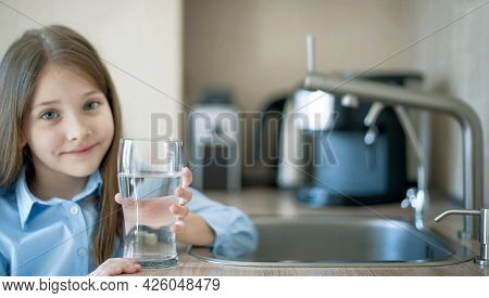 Little Girl Drinking From Water Tap Or Faucet In Kitchen. Pouring Fresh Drink. Healthy Lifestyle. Wa