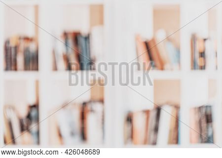Bookshelves With Books In Library, Soft Focus. Abstract Blurred Light Background. Concept Of Learnin