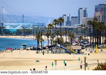 June 6, 2021 In Long Beach, Ca:  People On A Sandy Beach Besides The Pacific Ocean And The Downtown