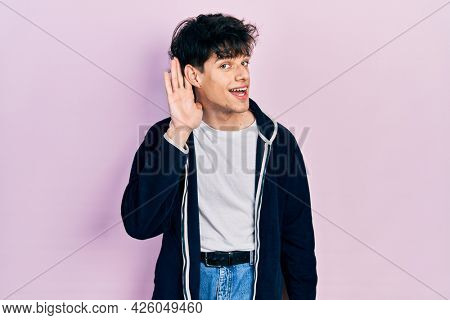 Handsome hipster young man wearing casual white t shirt and sweatshirt smiling with hand over ear listening and hearing to rumor or gossip. deafness concept.