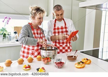 Senior caucasian couple smiling happy baking sweets using touchpad at the kitchen.