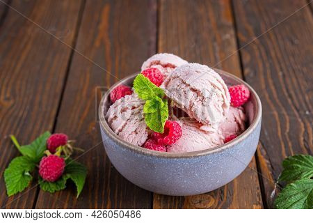 Balls Of Raspberry Ice Cream With Fresh Raspberries In A Ceramic Bowl On A Brown Wooden Background.