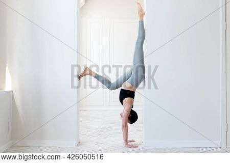 A Young Woman Practices Yoga And Stands On Her Arms In The Arch Of A Bright Room. Young Attractive Y