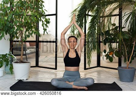 Young Woman Meditating Indoors. Pose Young Woman Smiling For The Camera, Sitting In The Lotus Positi