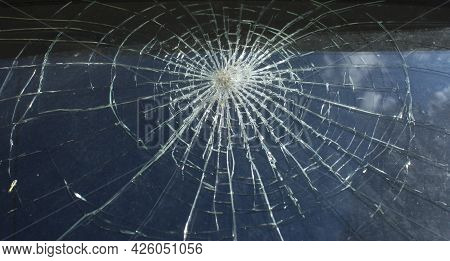 Broken Glass With Cracks On Blue Sky Background. Close Up View Of Broken Glass Texture