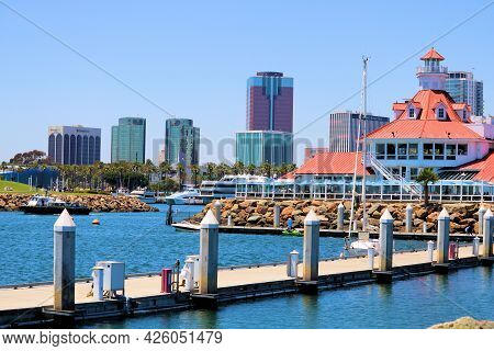July 6, 2021 In Long Beach, Ca:  Sailboat Docked On A Visitors Pier With A Building Which Replicates