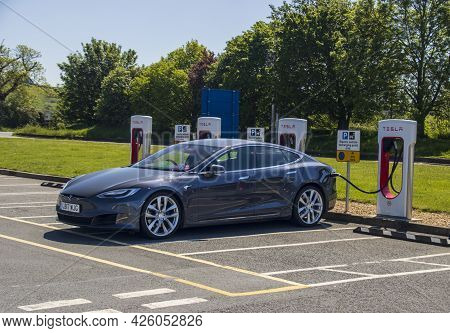 Grantham, Uk - May 30th 2021: Tesla Saloon Plugged Into A Supercharger