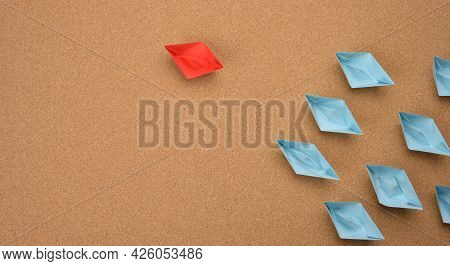 Group Of Paper Boats On A Brown Background. Concept Of A Strong Leader In A Team, Manipulation Of Th